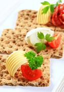 Whole grain crispbread with various toppings - stock photo