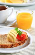 Stock Photo of Bread with butter, cup of tea and orange juice