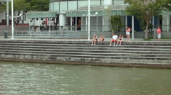 Tourists sitting on the banks of Singapore River Stock Footage