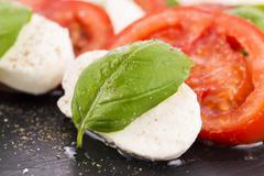Caprese salad with mozzarella, tomato, basil and balsamic vinegar arranged on bl - stock photo