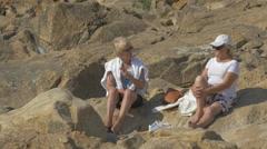 Women sitting on rocks in front of Castelo do Queijo, Porto Stock Footage