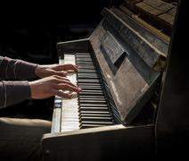 Hands of man playing an old piano - stock photo