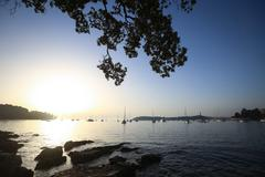 Sailboats at sunset anchored in Adriatic sea - stock photo