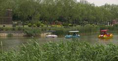 4K People Ride Paddle Boats on a Park Lake in China - 2 Shot Combo Stock Footage