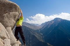 Climbing young adult at the top of summit Stock Photos