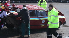 Rescue team turning wrecked car around at extreme stunt show Stock Footage
