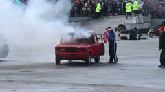 Viewers watching senior man extinguish stunt car fire, sequence Stock Footage