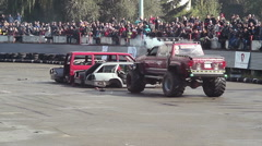Two Bigfoot trucks destroying old cars at show, huge wheels Stock Footage