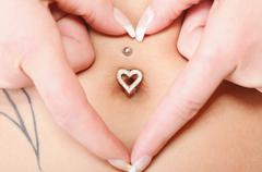 Stock Photo of hands heart symbol around navel piercing