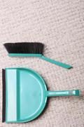 Stock Photo of Green sweeping brush and dustpan for house work on floor indoors. Cleaning