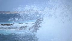 SLOW MOTION: Rough sea hitting into rocks and splashing high - stock footage