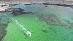 AERIAL: Kitesurfer speeding with kite in flat water lagoon Stock Footage