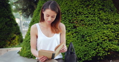 Young girl is reading in the park - stock footage