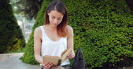 Stock Video Footage of Young girl is reading in the park