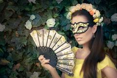 Beautiful Woman with Floral Wreath, Mask and Fan - stock photo