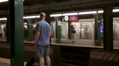 Subway train other side of tracks departing station man waiting train platform Stock Footage
