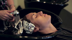 Close-up hands rinsing woman's hair dye tin foil - highlight treatment in salon Stock Footage