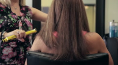 Back of woman's head - beauty salon - long hair being straightened hair iron Stock Footage
