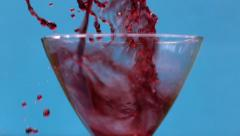 Ice dropped into red wine glass, slow motion 500fps Stock Footage
