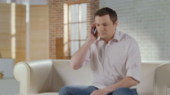 Young man discussing business problems in phone call at home Stock Footage