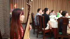A beautiful female artist playing Pipa (chinese traditional lute) in the dinner Stock Footage