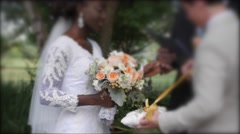 Caucasian male putting ring on African America bride Stock Footage