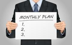 Businessman holding monthly plan words poster Stock Illustration