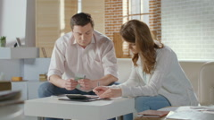 Couple calculating income and expenses, low family budget, money - stock footage