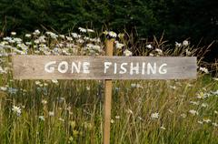 Gone Fishing sign among flowers - stock photo