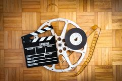 Movie clapper board and film reel on wooden floor - stock photo