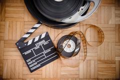 Cinema movie clapper board and film reel Stock Photos