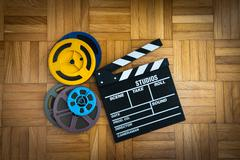 Movie clapper board and film reel on wooden floor Stock Photos