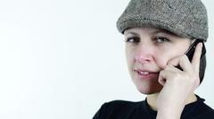 Flat cap, beautiful green eyed woman, she talk on phone, close up Stock Footage