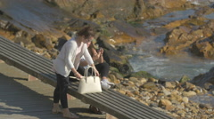 Two girls watching their phone on the sidewalk along the ocean, Porto Stock Footage