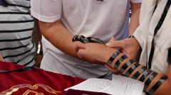 Father Wraps Tefillin on Son's Hand in 4K Stock Footage