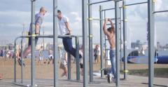 Men doing strength exercises on a pull-up gym at the beach Stock Footage