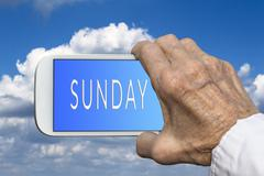 Stock Photo of Smart phone in old hand with days of the week - Sunday on screen