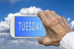 Smart phone in old hand with days of the week -  Tuesday on screen - stock photo