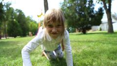 Girl and boy crawls on all fours on the grass Stock Footage