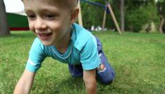 The boy crawls on all fours on the grass Stock Footage