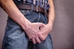 Man in jeans covers his crotch with hands - stock photo