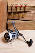 Fishing reel with metal lures. - stock photo