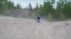 Dirtbike drop off jump straight on view Stock Footage