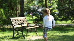 The girl ran and sat on the bench Stock Footage