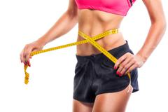 Weight losing - measuring woman's body - stock photo