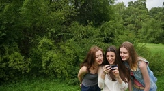 Three friends, young girls, having fun in park, making selfie, slow motion. Stock Footage