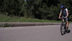 Male Riding Bike Along Park Road Stock Footage