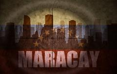 sniper scope aimed at the abstract silhouette of the city with text Maracay a - stock illustration
