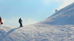 Snowboarders performing dangerous tricks on snowy mountain slope Stock Footage
