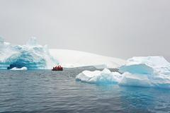 Tourists in a boat in the Antarctic - stock photo
